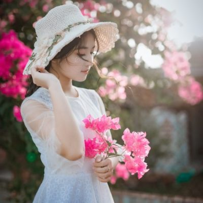 woman-wearing-sun-hat-and-white-dress-holding-pink-1382734